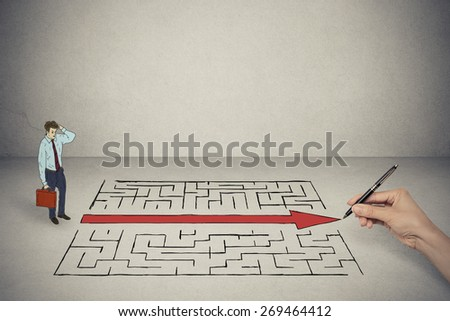 Business man looking at hand drawing solution for maze - stock photo