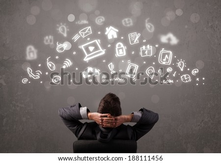 Business man looking at modern icons and symbols concept - stock photo