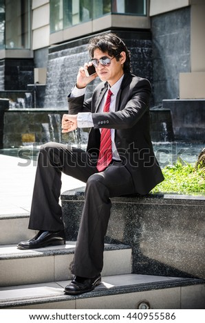 business man looking at watch and talking on cell phone - stock photo