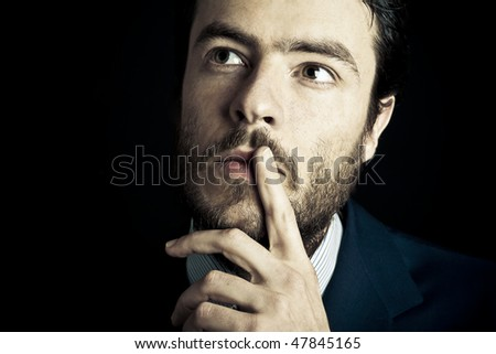 Business man looking for inspirations and ideas isolated on black background - stock photo