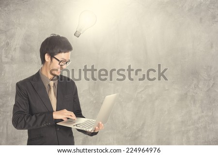 Business man looking laptop and concrete wall background