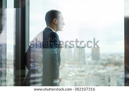 Business man looking out through the office balcony seen through glass doors. - stock photo