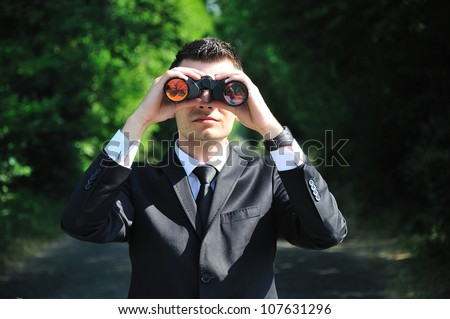 Business man looking with binocular - stock photo