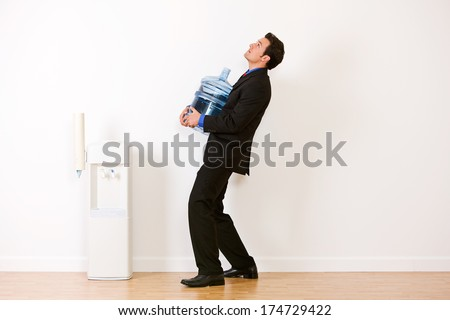 Business: Man Lugging Jug To Water Cooler - stock photo
