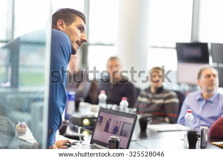 Business man making a presentation at office. Business executive delivering a presentation to his colleagues during meeting or in-house business training, explaining business plans to his employees. - stock photo