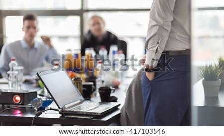Business man making a presentation at office. Business executive delivering a presentation to his colleagues during meeting or in-house business training. Rear view. Business and entrepreneurship. - stock photo