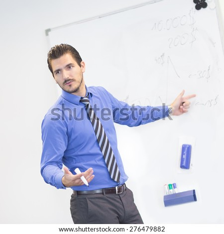 Business man making a presentation in front of whiteboard. Business executive delivering a presentation to his colleagues during meeting or in-house business training, explaining business plans. - stock photo