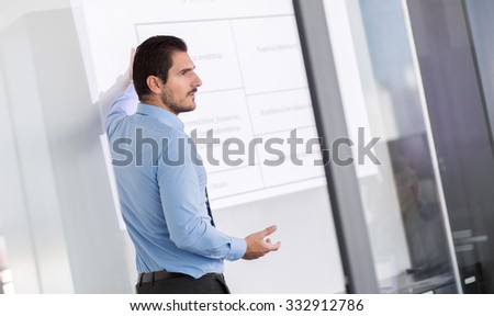 Business man making a presentation in front of whiteboard. Business executive delivering a presentation to his colleagues during meeting or in-house business training.  - stock photo