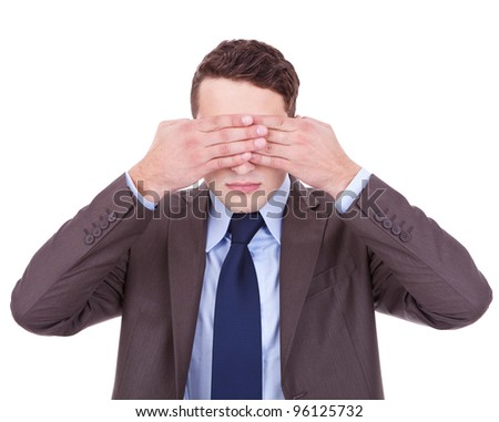 business man making the see no evil gesture over white . young businessman covering his eyes with his hand - stock photo