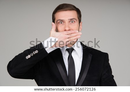 Business man making the speak no evil gesture. Businessman covering his mouth with his hand - stock photo