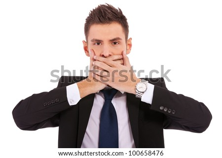 business man making the speak no evil gesture over white . young businessman covering his mouth with his hand - stock photo