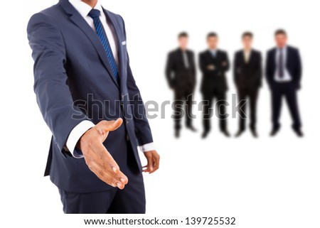Business man offering handshake with businesspeople people on background - stock photo
