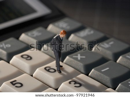 Business man on financial calculator concept - stock photo
