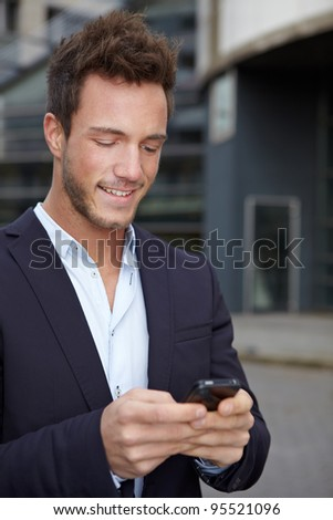 Business man on the run in city checking cell phone for new messages - stock photo