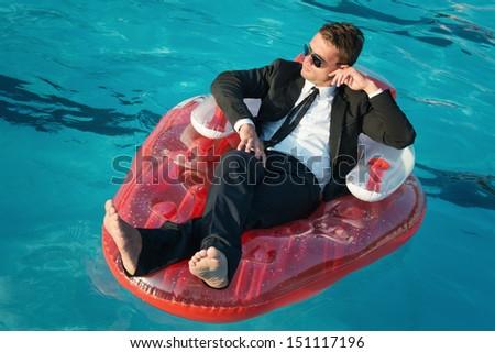business man on the swimmingpool - stock photo