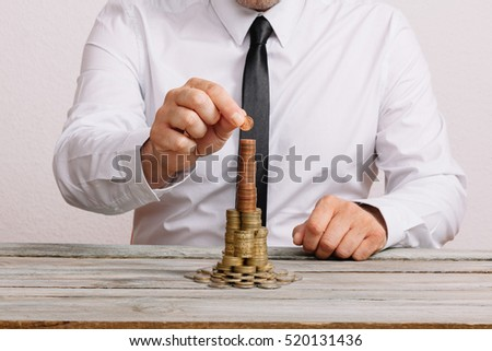 Business man on wood table, building stack of coins, building savings, financial concept image.