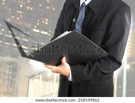business man open document file double exposure building night light - stock photo