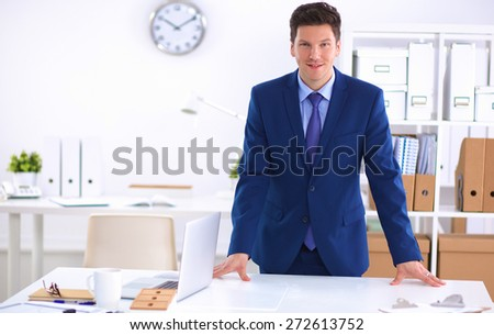 Business man or manager standing against his desk at the office. - stock photo