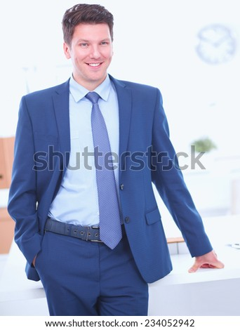 Business man or manager standing against his desk at the office isolated - stock photo