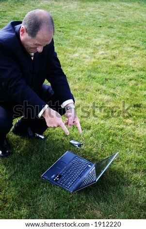 Business man outdoors in the grass pointing at laptop - stock photo