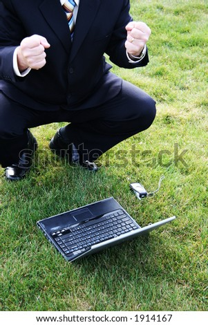 Business man outdoors in the grass with laptop