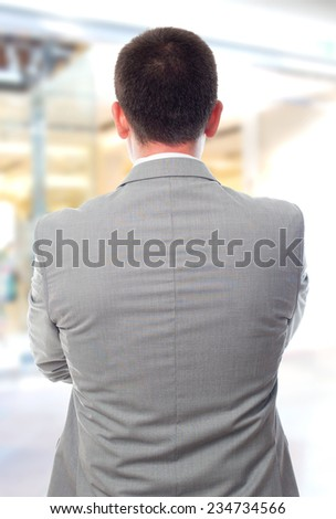 Business man over shopping center background. Giving his back - stock photo