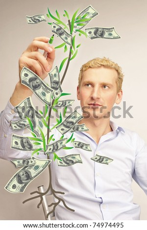 business man painting tree on a transparent touchscreen with his marker - stock photo