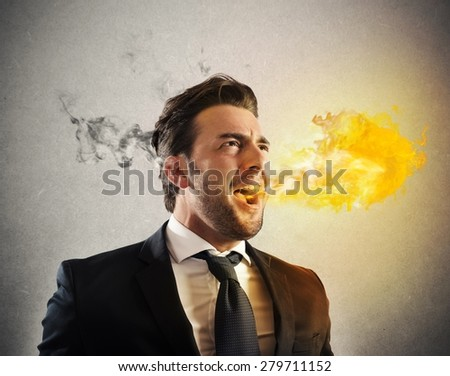 Business man pissed and furious spitting fire - stock photo