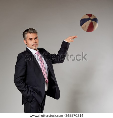 Business man playing with a basketball at the studio - stock photo