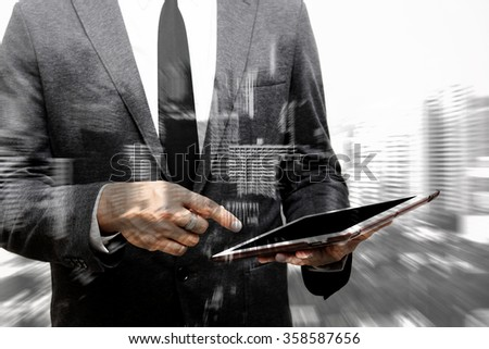 business man point at computer tablet composite with blur building - stock photo