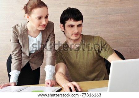 Business man pointing at laptop and explaining a plan of work to colleague