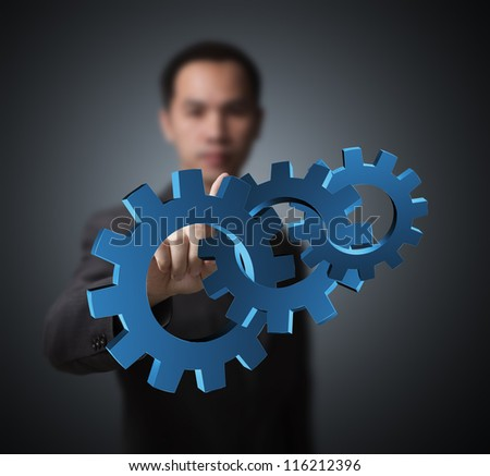 business man pointing at set of gears, concept of industry, machine, teamwork, power, and advance - stock photo