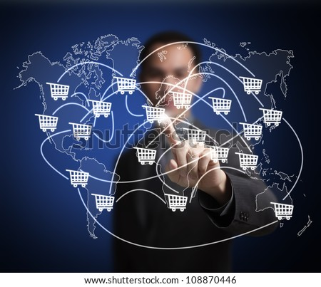business man pointing at worldwide cart network on world map -  symbol of modern online trade and marketing - stock photo