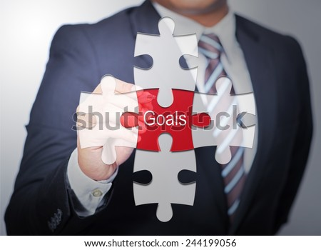 Business Man pointing on jigsaw written word Goals - stock photo
