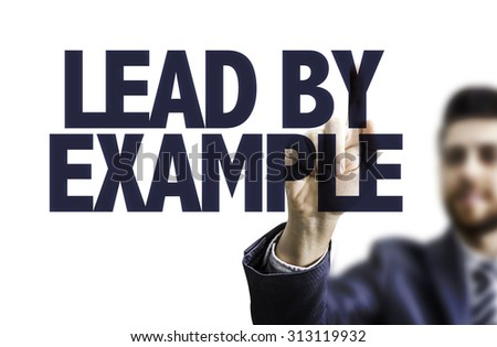 Business man pointing the text: Lead by Example - stock photo