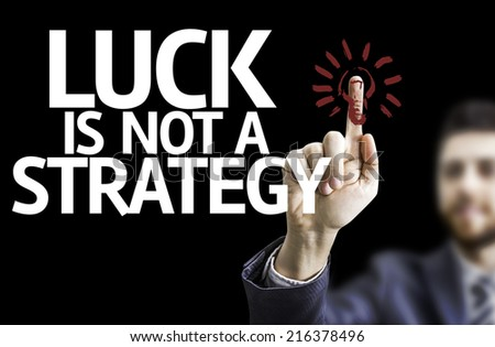 Business man pointing to black board with text: Luck is Not a Strategy - stock photo