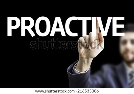 Business man pointing to black board with text: Proactive - stock photo