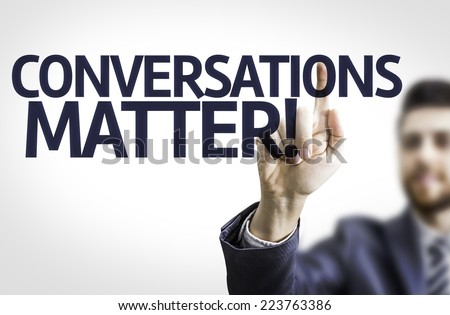 Business man pointing to transparent board with text: Conversations Matter - stock photo