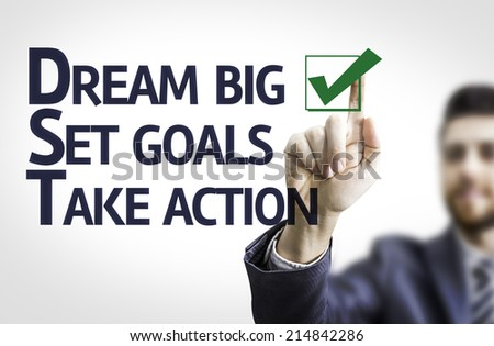Business man pointing to transparent board with text: Dream Big / Seat Goals / Take Action - stock photo