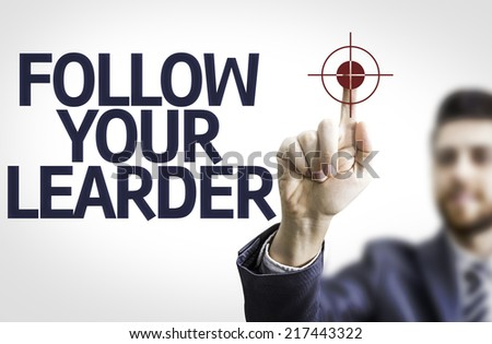 Business man pointing to transparent board with text: Follow your Leader - stock photo