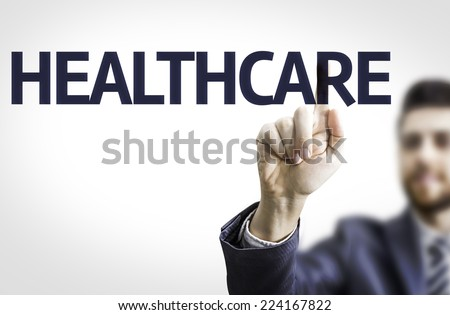 Business man pointing to transparent board with text: Healthcare - stock photo