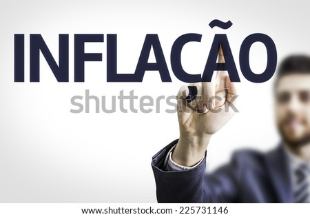 Business man pointing to transparent board with text: Inflation (In Portuguese) - stock photo