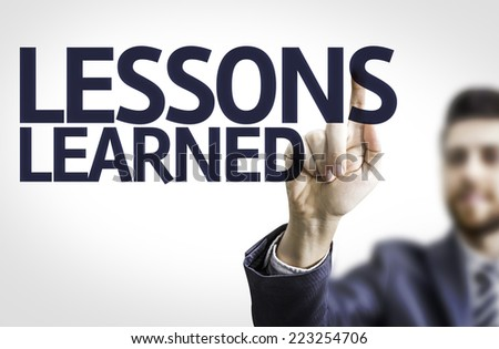 Business man pointing to transparent board with text: Lessons Learned - stock photo