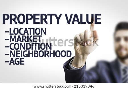Business man pointing to transparent board with text: Property Value  - stock photo