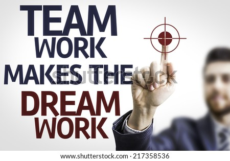 Business man pointing to transparent board with text: Team Work Makes the Dream Work - stock photo
