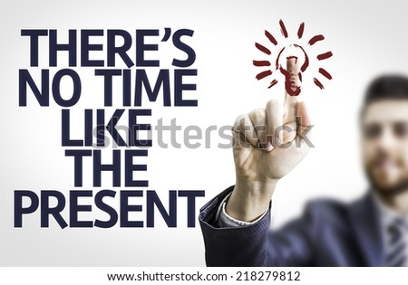 Business man pointing to transparent board with text: There's no Time Like the Present - stock photo