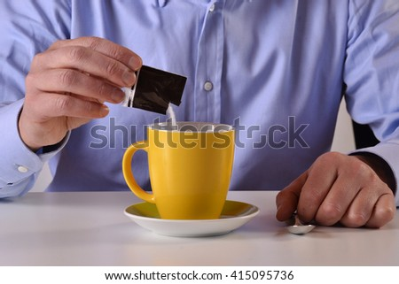 Business man pouring sugar bag on yellow coffee cup - stock photo