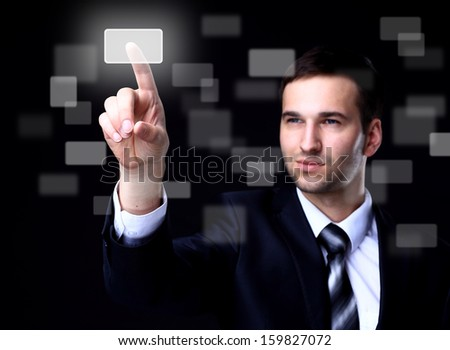 business man pressing a touchscreen button on dark background - stock photo