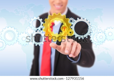 business man pushing a cog button on a word map background - stock photo