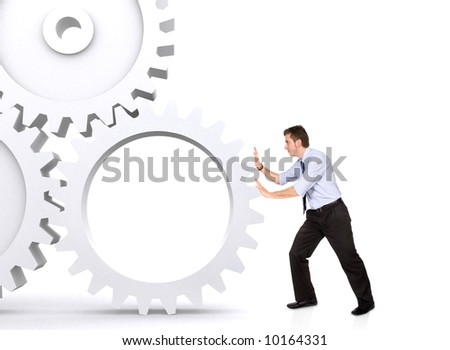 business man pushing a cogwheel to make it work - stock photo